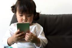 Hållande ögonen på tecknad film för liten flicka på mobila enheten Royaltyfria Bilder