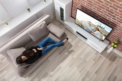 Hållande ögonen på television för kvinna hemma arkivbilder