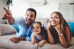 Hållande ögonen på television för lycklig familj på deras hem arkivbild