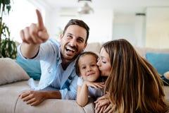 Hållande ögonen på television för lycklig familj på deras hem royaltyfri fotografi
