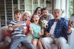 Hållande ögonen på television för lycklig familj i vardagsrum arkivfoton