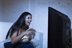 Hållande ögonen på television för lycklig kvinna på popcorn för äta för soffasoffa lyckligt upphetsat tyckande om Arkivbild