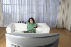 Hållande ögonen på television för lycklig man på soffan  Arkivfoton