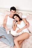 Hållande ögonen på television för lyckliga par tillsammans Fotografering för Bildbyråer