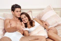 Hållande ögonen på television för lyckliga par tillsammans Arkivfoton