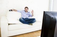 Hållande ögonen på television för man på vardagsrumsoffan med fjärrkontroll som ler ge bra handtecknet Fotografering för Bildbyråer