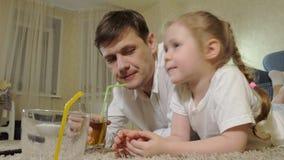 Hållande ögonen på television för man som och för dotter sitter på golvdrinkfruktsaften lager videofilmer