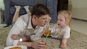 Hållande ögonen på television för man som och för dotter sitter på golvdrinkfruktsaften stock video