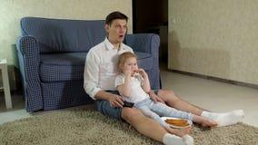 Hållande ögonen på television för man som och för dotter sitter på golvet som äter mellanmål arkivfilmer