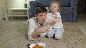 Hållande ögonen på television för man som och för dotter sitter på golvet som äter mellanmål lager videofilmer