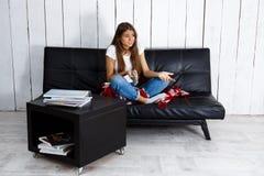 Hållande ögonen på television för missnöjd härlig flicka som hemma sitter på soffan arkivbilder