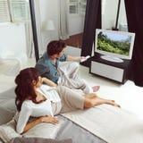 Hållande ögonen på television för par Royaltyfri Foto