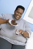 Hållande ögonen på television för sjukligt fet man Arkivfoton