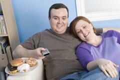 Hållande ögonen på television för sjukligt feta par Royaltyfri Fotografi