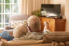 Hållande ögonen på television för tillgivna höga par tillsammans på deras soffa arkivfoto