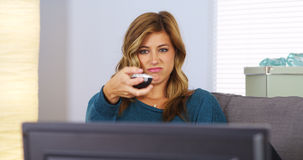 Hållande ögonen på television för ung kvinna med fjärrkontrollen i hand Royaltyfri Foto