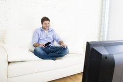 Hållande ögonen på television för ung lycklig man som ler och skrattar i soffa Arkivfoton
