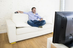 Hållande ögonen på television för ung lycklig man som ler och skrattar i soffa Arkivbilder