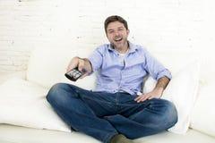 Hållande ögonen på television för ung lycklig man som ler och skrattar i soffa Fotografering för Bildbyråer