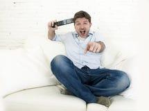 Hållande ögonen på television för ung lycklig man som ler och skrattar i soffa Royaltyfri Foto