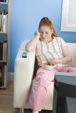 Hållande ögonen på television för uttråkad sjukligt fet flicka Arkivfoton