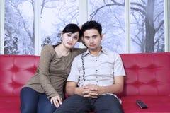 Hållande ögonen på television för uttråkade par hemma Arkivbild