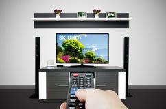 Hållande ögonen på television i modernt TVrum Jämför av televisionupplösning Arkivfoto