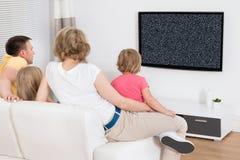 Hållande ögonen på televisionvisning för familj ingen signal royaltyfri foto