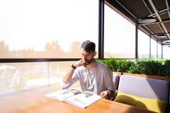 Hållande ögonen på tidskriftbilder för stilig illustratör på tabellen arkivfoton