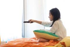 Hållande ögonen på TV för asiatisk flicka som ligger på säng med fjärrkontroll i hand royaltyfria foton