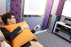 Hållande ögonen på TV för asiatisk man i rum för hem- teater arkivbilder