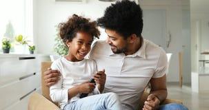 Hållande ögonen på tv för avkopplad afrikansk amerikanfamilj arkivfoto