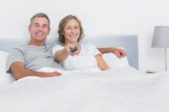 Hållande ögonen på tv för avkopplade par i säng som ser kameran arkivfoto