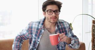 Hållande ögonen på tv för förvånad man, medan dricka kaffe stock video