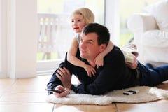 Hållande ögonen på tv för fader och för dotter hemma royaltyfri fotografi