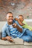 Hållande ögonen på tv för fader och för son tillsammans på soffan Royaltyfria Foton