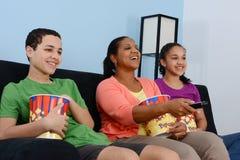 Hållande ögonen på TV för familj Arkivfoto
