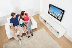 Hållande ögonen på TV för familj hemma Arkivfoton