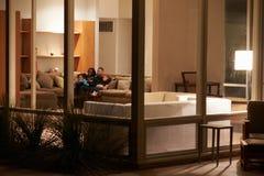 Hållande ögonen på TV för familj hemma som utifrån beskådas Arkivbilder