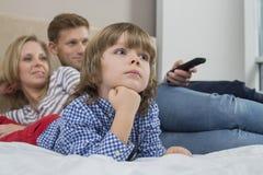 Hållande ögonen på TV för familj i sovrum Arkivbild