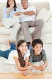 Hållande ögonen på tv för familj i vardagsrumet Royaltyfri Bild