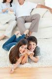 Hållande ögonen på tv för familj i vardagsrumet Fotografering för Bildbyråer