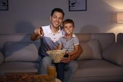 Hållande ögonen på TV för familj med popcorn i rum på tid royaltyfri fotografi