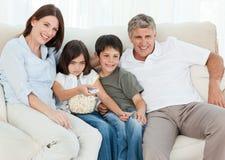 Hållande ögonen på tv för familj, medan de äter popcorn Royaltyfri Foto