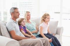 Hållande ögonen på TV för familj, medan sitta på soffan Fotografering för Bildbyråer