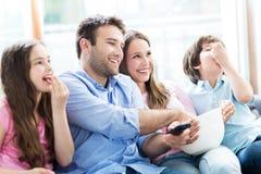 Hållande ögonen på tv för familj och ätapopcorn arkivbilder