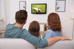 Hållande ögonen på tv för familj på soffan arkivfoton