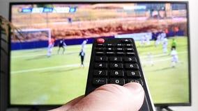 Hållande ögonen på TV för fjärrkontroll i bakgrund arkivfoton