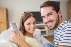Hållande ögonen på tv för gulliga par på soffan Royaltyfria Bilder