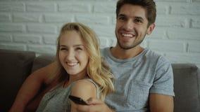 Hållande ögonen på tv för häpna par att programmera sammanträde på en soffa hemma